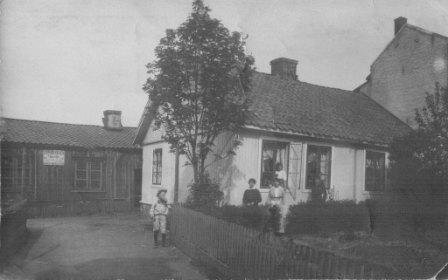 """""""Dette bildet er fra Etterstadgata 8, og det er mitt barndomshjem. Utenfor huset, paa veien er min bror Alf. Paa plenen er søstrene mine Asta og Gulborg og i vinduet min søster Emma. Min far var laasesmedmester, tok over smia etter min bestefar. Her ble det laget laaser for hånd, var jo ikke elektrisitet den gangen."""
